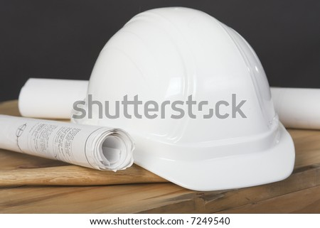 Closeup shot of a construction hardhat and blueprints - stock photo