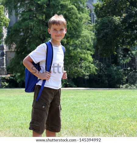 closeup shot of a happy young boy carrying a backpack standing in a park of school  - school concept - stock photo