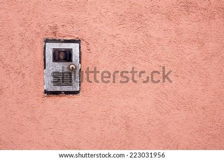 Closeup shot of a intercom on a red wall - stock photo