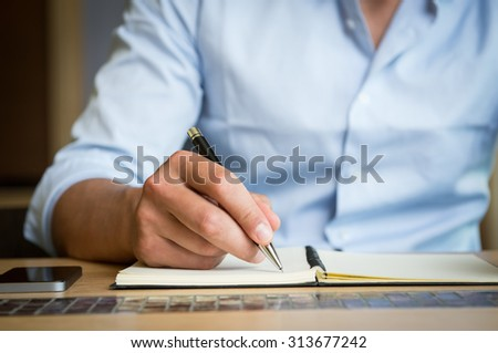 Closeup shot of a man taking down note in a personal organizer. Young man's hand writing in diary. Close up of hand of a businessman writing on a business plan. - stock photo