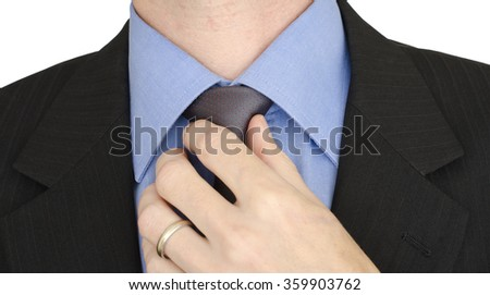 Closeup shot of a neck section as man adjusts necktie. Left hand pinches Windsor knot on silver colored tie with red spots. Man is wearing dark suit and light blue shirt.  - stock photo