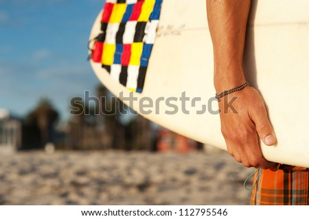closeup shot of a surfer holding a surfboard at the beach - stock photo