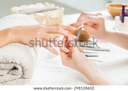Closeup shot of a woman in a nail salon receiving a manicure by a beautician with nail file. Woman getting nail manicure. Beautician file nails to a customer. - stock photo