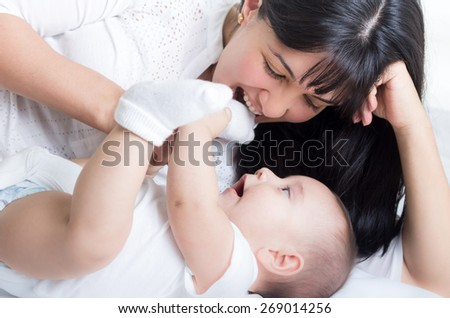 closeup shot of beautiful young mom staring at her small cute baby  - stock photo