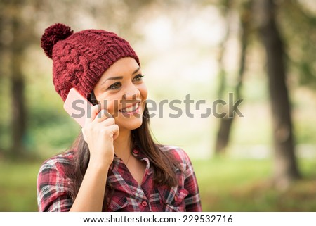 Closeup shot of beautiful young woman with maroon beanie hat talking on the phone smiling outdoors in park in autumn. No retouch.