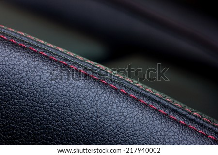 closeup shot of black leather car seat with red stitch   - stock photo