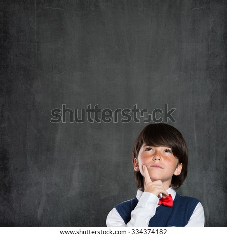 Closeup shot of boy thinking with hand on chin isolated on blackboard. Portrait of pensive child thinking about his academic future. Child have an idea. - stock photo
