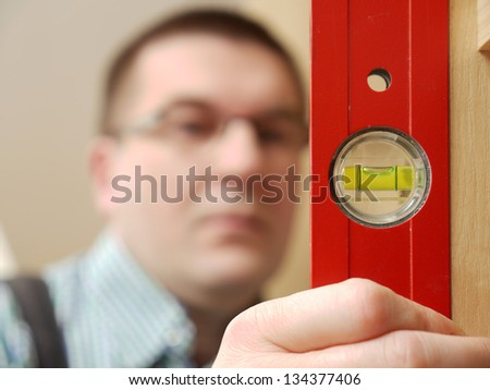 Closeup shot of carpenter looking at spirit level gauge to check verical positioning of furniture - shallow depth of field - stock photo