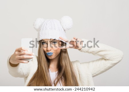 Closeup shot of cute teenage girl with blue lips and white knit hat taking a selfie with smart phone pouting and showing two fingers. Modern hipster young woman photographing herself with cellphone. - stock photo