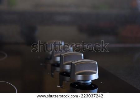 closeup shot of elegant and black stove knobs - stock photo