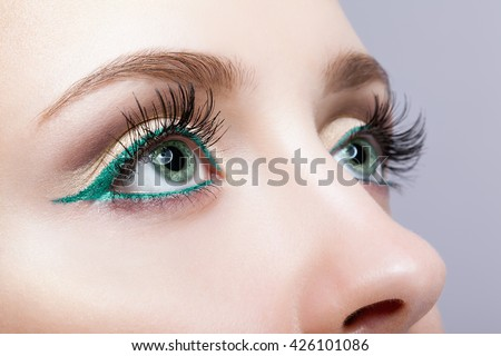 Closeup shot of female face makeup with pistachio colour eyes  and green eyeliner - stock photo
