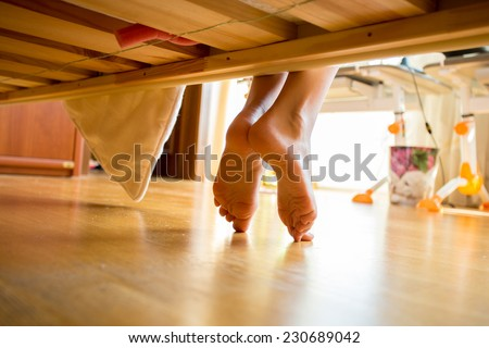Closeup shot of female feet under bed at morning - stock photo