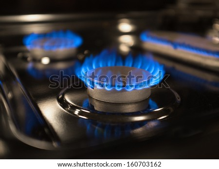 Closeup shot of fire from gas kitchen stove - stock photo