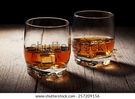Closeup shot of glasses filled with whiskey and ice in backlight - stock photo