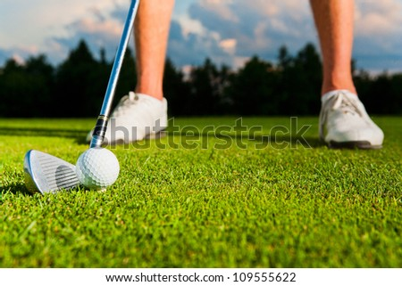 closeup shot of golf ball with golf club right before tee off - stock photo