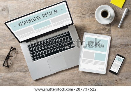 Closeup shot of laptop with digitaltablet and smartphone on desk. Responsive design web page on their screen. Modern devices on desk at office. 