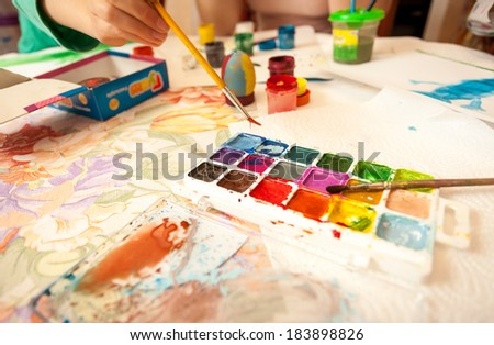 Closeup shot of little girl holding brush and taking watercolor - stock photo