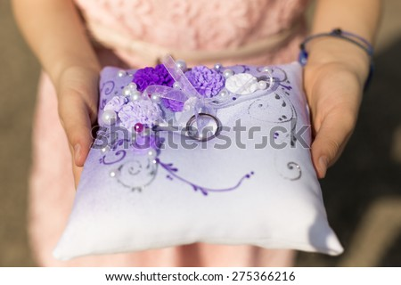 Closeup shot of little girl holding cushion with wedding rings - stock photo