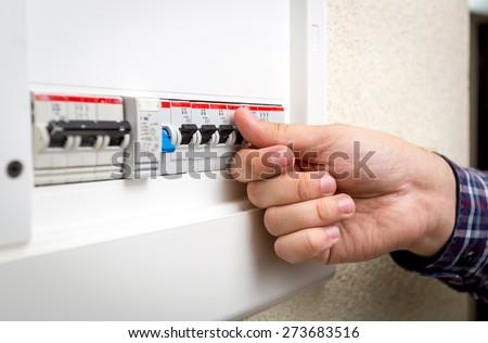 Closeup shot of man switching on fuseboard - stock photo