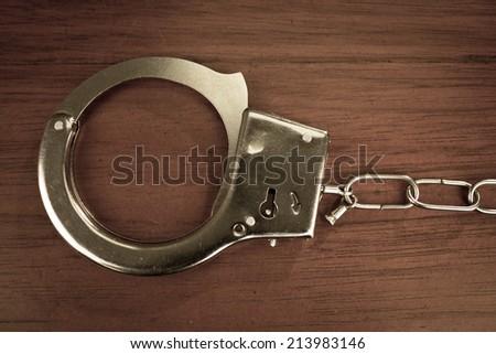 Closeup shot of metallic handcuffs over wooden background - stock photo