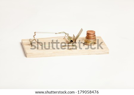 Closeup shot of mouse trap with pile of coins as bait - stock photo