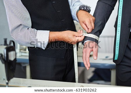 Closeup shot of old-fashioned tailor taking wrist measurements from client in small atelier studio to make custom classic suit with jacket