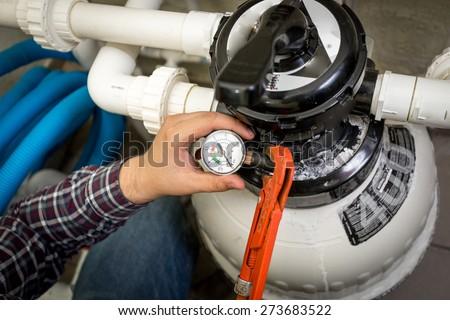 Closeup shot of plumber checking manometer on big hydraulic pump - stock photo