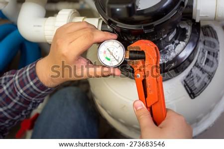 Closeup shot of plumber installing manometer on pipe - stock photo