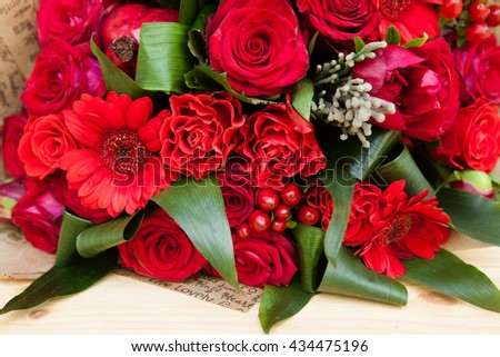 Closeup shot of red bouquet of roses, gerberas, peonies, pomegranates. Love and passion symbol. Anniversary or birthday gift for girl. - stock photo