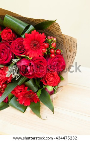 Closeup shot of red bouquet of roses, gerberas, peonies, pomegranates with copy space. Love and passion symbol. Anniversary or birthday gift for girl. - stock photo