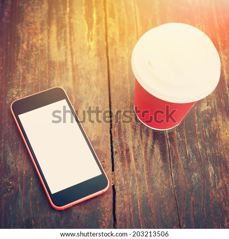 Closeup shot of smart phone white isolated white screen and red cup of takeaway coffee on wooden surface table outdoors. Sunlit. Square image. Instant filter. Contemporary concept. Mock-up.  - stock photo