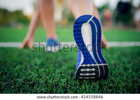 Closeup shot of the feet of a woman at the starting line on grass.  Getting ready for a race - stock photo