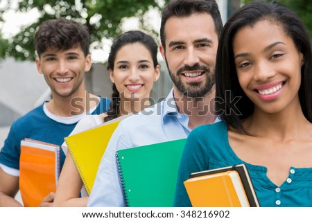 Closeup shot of university students standing in a row with books. Happy and smiling group of men and women holding book outddor. Happy young friends holding book and notebook outside the university.
