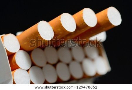 Closeup shot of white pack of cigarettes on a black background. - stock photo