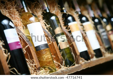 Closeup shot of wineshelf. Bottles lay over straw. - stock photo