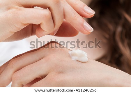 Closeup shot of woman hands applying moisturizing hand cream