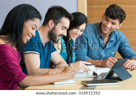 Closeup shot of young man and woman discussing on note. Happy smiling students preparing the exam. Team of students studying together for the university exam.  - stock photo