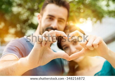 Closeup shot of young man and woman making heart shape with hand. Loving couple making heart shape with hands outdoor. Female and male hands making up heart shape. - stock photo
