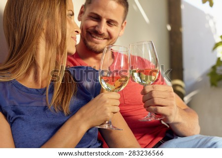 Closeup shot of young man and woman sitting together toasting wine glasses. Couple in love spending romantic time together. - stock photo