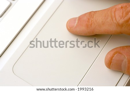 Closeup showing fingers using laptop touchpad