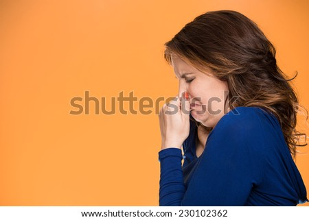 Closeup side profile portrait unhappy middle age woman covers pinches  her nose something stinks very bad smell situation, isolated orange background with copy space. Human facial expression emotion - stock photo