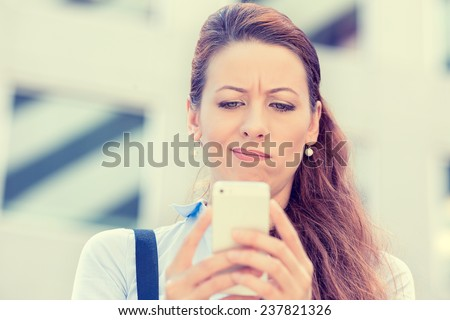 Closeup side profile portrait upset sad skeptical unhappy serious woman talking texting on phone displeased with conversation isolated city background. Negative human emotion face expression feeling - stock photo
