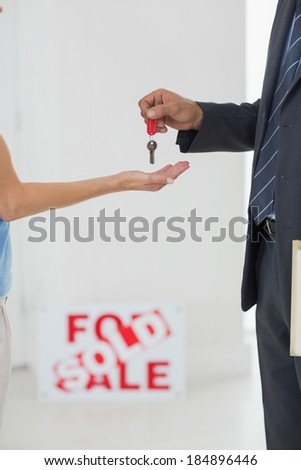 Closeup side view mid section of passing over house key - stock photo