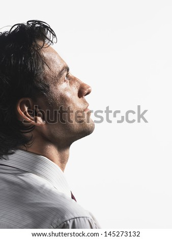 Closeup side view of a tired young businessman staring into space against white background - stock photo