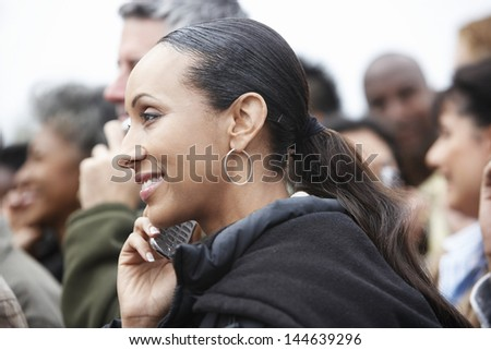 Closeup side view of an African American woman using cellphone in blurred crowd - stock photo