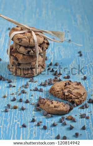 Closeup side view of broken cookie and tied biscuits with chocolate drops on cracked blue background - stock photo