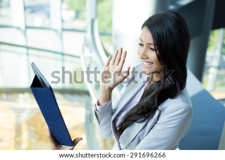 Closeup side view portrait, attractive woman in gray business suit waving saying hi gesture on tablet, isolated indoors office background - stock photo