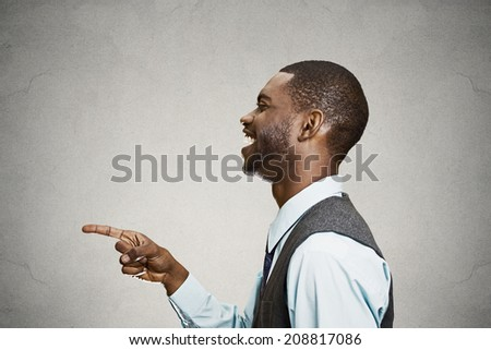 Closeup side view portrait happy young man, laughing, pointing with finger at someone, something, isolated grey background. Positive human face expressions, emotions, feelings, attitude, approach - stock photo