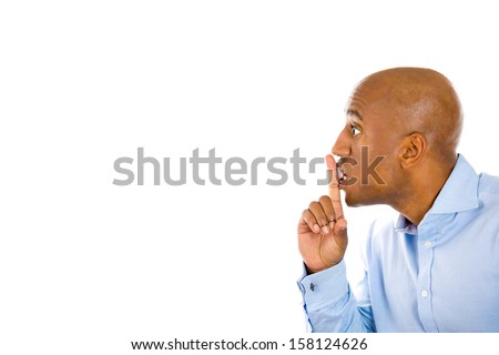Closeup side view portrait of a young, serious, man placing finger on lips as if to say, shhhhh, be quiet, silence , isolated on white background with copy space. Facial expression, human emotions. - stock photo
