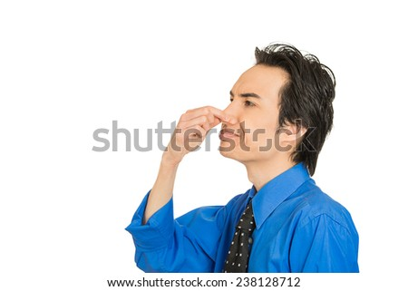Closeup side view portrait young man disgust on his face pinches his nose, something stinks, very bad smell, situation isolated white background with copy space. Negative emotion expression feeling - stock photo